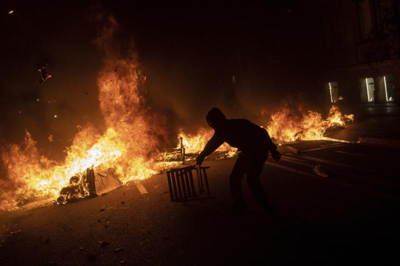 A protester drags a chair next to a burning barricade during clashes with police in Barcelona, Spain, Tuesday, Oct. 15, 2019. Spain's Supreme Court on Monday convicted 12 former Catalan politicians and activists for their roles in a secession bid in 2017, a ruling that immediately inflamed independence supporters in the wealthy northeastern region. (Photo: Bernat Armangue/AP)