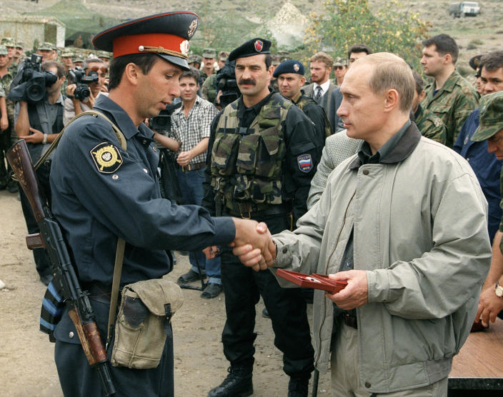 Russia's then-Prime Minister Vladimir Putin, right, presents an award to a local police officer at a Russian military base in the mountains of the Botlikh region, Dagestan, Russia, Aug. 27, 1999. (Photo: AP)