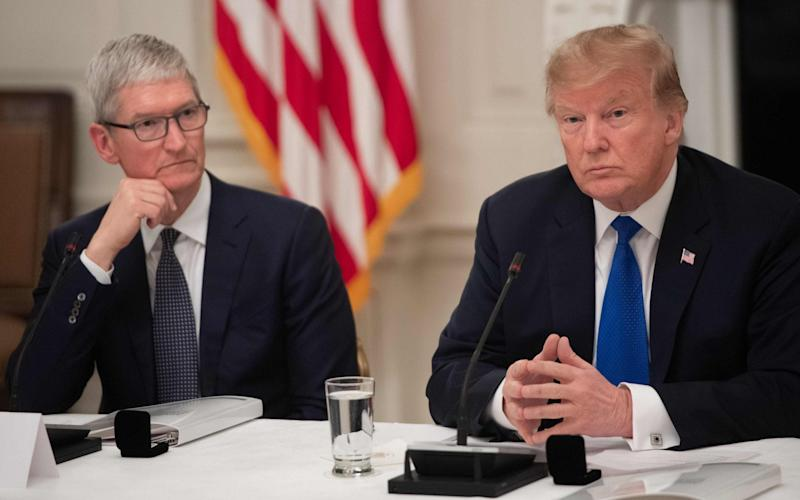 Tim Cook and Donald Trump are at loggerheads for the second time in four years over unlocking iPhones - AFP
