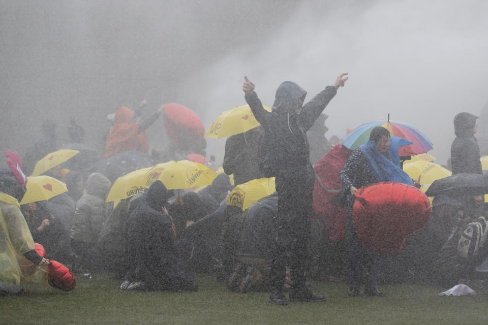 Police use a water cannon to break up a demonstration against coronavirus related government policies including the curfew and the tight lockdown in Amsterdam, Netherlands, Sunday, March 28, 2021. (AP Photo/Peter Dejong)