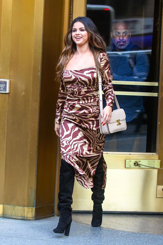 Selena looks totally set for fall in this patterned long-sleeved dress and knee high boots. She completed the look with a chic purse.
