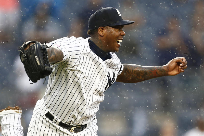 Jul 31, 2019; Bronx, NY, USA; New York Yankees pitcher Aroldis Chapman (54) reaches for a ball against the Arizona Diamondbacks during the ninth inning at Yankee Stadium. Mandatory Credit: Adam Hunger-USA TODAY Sports