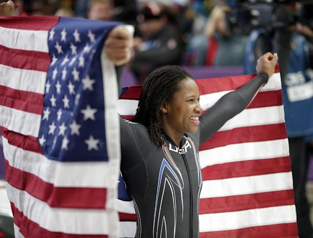 Silver medal winner Lauryn Williams holds the flag after the women's bobsled competition at the 2014 Winter Olympics, Wednesday, Feb. 19, 2014, in Krasnaya Polyana, Russia. (AP Photo/Michael Sohn)