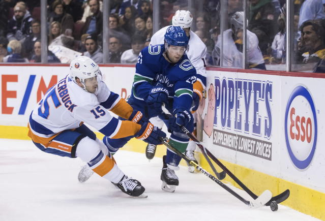 New York Islanders' Cal Clutterbuck (15) and Vancouver Canucks' Ben Hutton (27) reach for the puck during the first period of an NHL hockey game Saturday, Feb. 23, 2019, in Vancouver, British Columbia. (Darryl Dyck/The Canadian Press via AP)