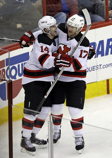 New Jersey Devils' Adam Henrique (14) and Michael Ryder (17) celebrate Henrique's goal against the Carolina Hurricanes during the third period of an NHL hockey game in Raleigh, N.C., Friday, Nov. 29, 2013. New Jersey won 5-2. (AP Photo/Gerry Broome)