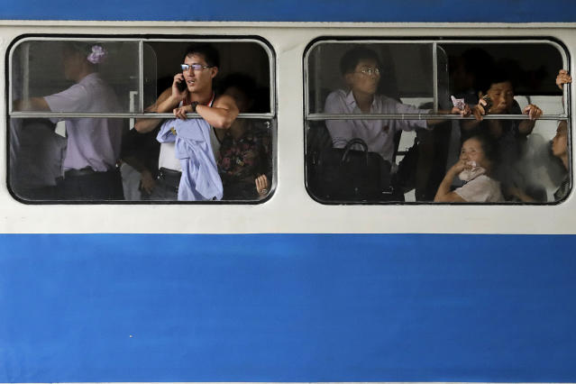 <p>A man talks on his mobile phone as he and other commuters ride in an electric trolley downtown Pyongyang at the end of a workday on July 28, 2017, in North Korea. (Photo: Wong Maye-E/AP) </p>
