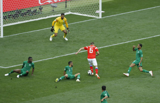 Russia's Denis Cheryshev dribbles past Saudi Arabia players to score his side's second goal during the 2018 soccer World Cup opening match at the Luzhniki stadium in Moscow, Russia, Thursday, June 14, 2018. (AP Photo/Victor Caivano)