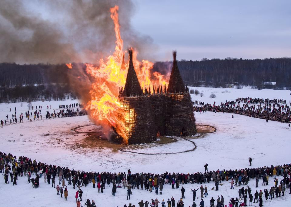 People watch a castle-shape wooden construction burning as part of celebrations at the Maslenitsa (Shrovetide) festival at the Nikola-Lenivets art park in Nikola-Lenivets village, about 200 kilometers (125 miles) southwest of Moscow, Russia, Saturday, March 13, 2021. Maslenitsa is an Orthodox Christian holiday celebrated in the last week before the Orthodox Lent. (AP Photo/Dmitry Serebryakov)