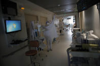 A nurse puts on protective clothing to tend to patients affected by the COVID-19 virus in the ICU unit at the Charles Nicolle public hospital, Thursday, April 15, 2021 in Rouen, France. A renewed crush of COVID-19 cases is again forcing intensive care units across France to grapple with the macabre mathematics of how to make space for thousands of critically ill patients (AP Photo/Christophe Ena)