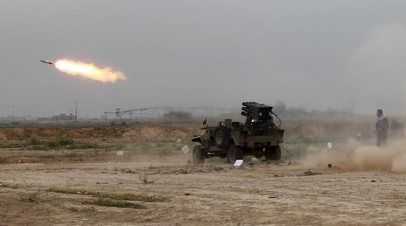 Iraqi Shiite fighters launch rockets towards fighters with the Islamic State (IS) group holed up in the centre of Tikrit, on March 12, 2015 (AFP Photo/Ahmad Al-Rubaye)
