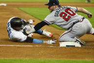 Atlanta Braves third baseman Josh Donaldson (20) tags out Miami Marlins' Miguel Rojas as he slid into third during the eighth inning of a baseball game, Sunday, June 9, 2019, in Miami. The Braves defeated the Marlins 7-6 in 12 innings. (AP Photo/Wilfredo Lee)