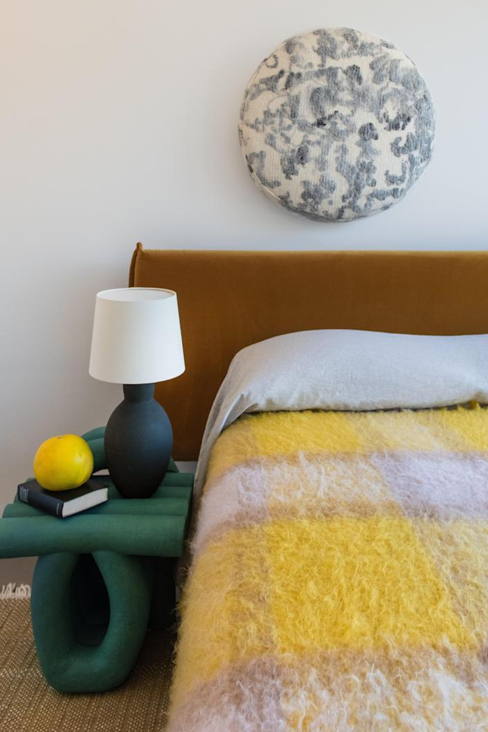 In the guest room, the green ceramic chair is by B Zippy, the ceramic lamp is by Catherine Raben Davidsen, and the wool blanket is by Mantas Ezcaray. The wool art is by JG Switzer.