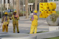 """Workers clean an area at Expo 2020 in Dubai, United Arab Emirates, Sunday, Oct. 3, 2021. Dubai's Expo 2020 on Saturday, Oct. 2, 2021, offered conflicting figures for how many workers had been killed on site during construction of the massive world's fair, first saying five and then later three. In a later statement, Expo apologized and described the initial figure as a """"mistake."""" (AP Photo/Jon Gambrell)"""