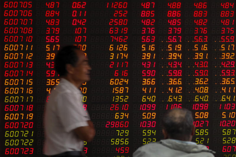 In this Oct. 16, 2019, photo, an investor walks by an electronic board displaying stock prices at a brokerage house in Beijing. Asian shares were mixed Monday, Oct. 21, amid uncertainties about Britain's exit from the European Union and the ongoing trade conflict  (AP Photo/Andy Wong)