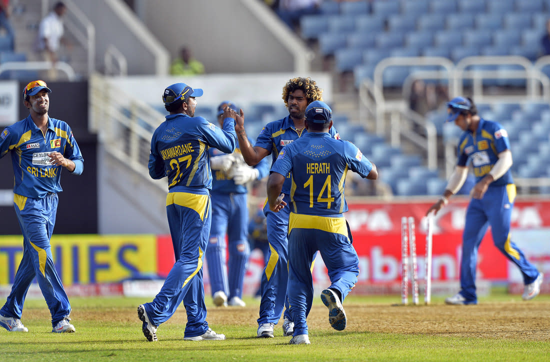 Sri Lankan cricketer Lasith Malinga (C) celebrates with teammates after dismissing the last wicket of India during the third match of the Tri-Nation series between India and Sri Lanka at the Sabina Park stadium in Kingston on July 2, 2013. Sri Lanka defeated India by 161 runs. AFP PHOTO/Jewel Samad