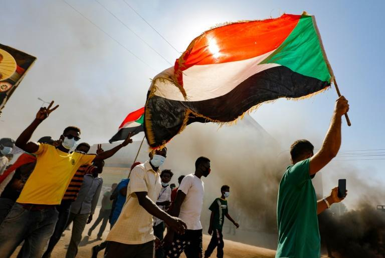 Sudanese demonstrators wave the national flag as they rally in the capital to mark the second anniversary of a revolt that toppled strongman Omar al-Bashir