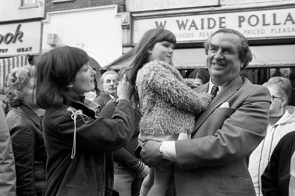 Chancellor of the Exchequer Denis Healey finds a friend in four year old Nina Westover when he toured the Ilford North constituency today in support of Labour's by-election candidate Mrs Tessa Jowell (left).   (Photo by PA Images via Getty Images)