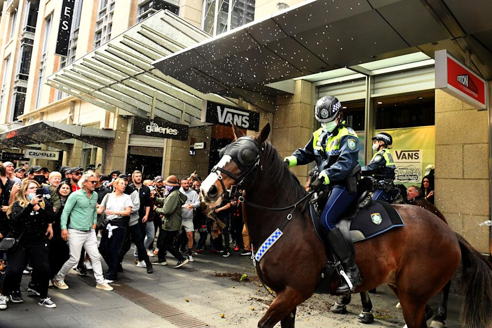 Protesters face off with mounted police at Sydney Town Hall during the anti-lockdown rally. Source: AAP