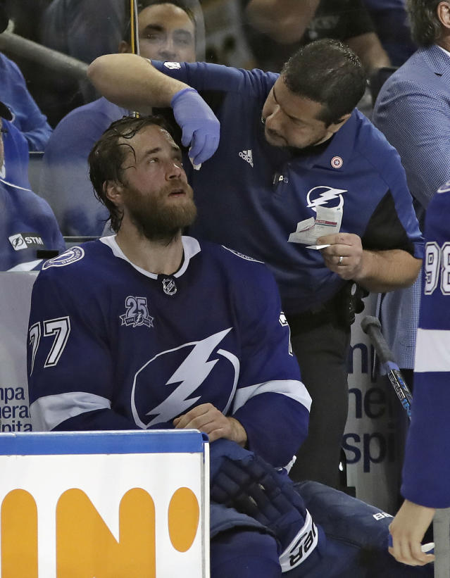 Tampa Bay Lightning trainer Tom Mulligan, right, cleans up a cut on defenseman Victor Hedman's face after he was cut with a high stick by Boston Bruins right wing David Pastrnak during the third period of Game 2 of an NHL second-round hockey playoff series Monday, April 30, 2018, in Tampa, Fla. Pastrnak was penalized four minutes. (AP Photo/Chris O'Meara)