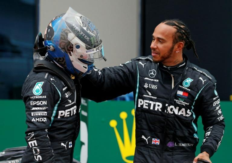 Lewis Hamilton is congratulated by Mercedes teammate Valtteri Bottas after winning a seventh drivers' crown