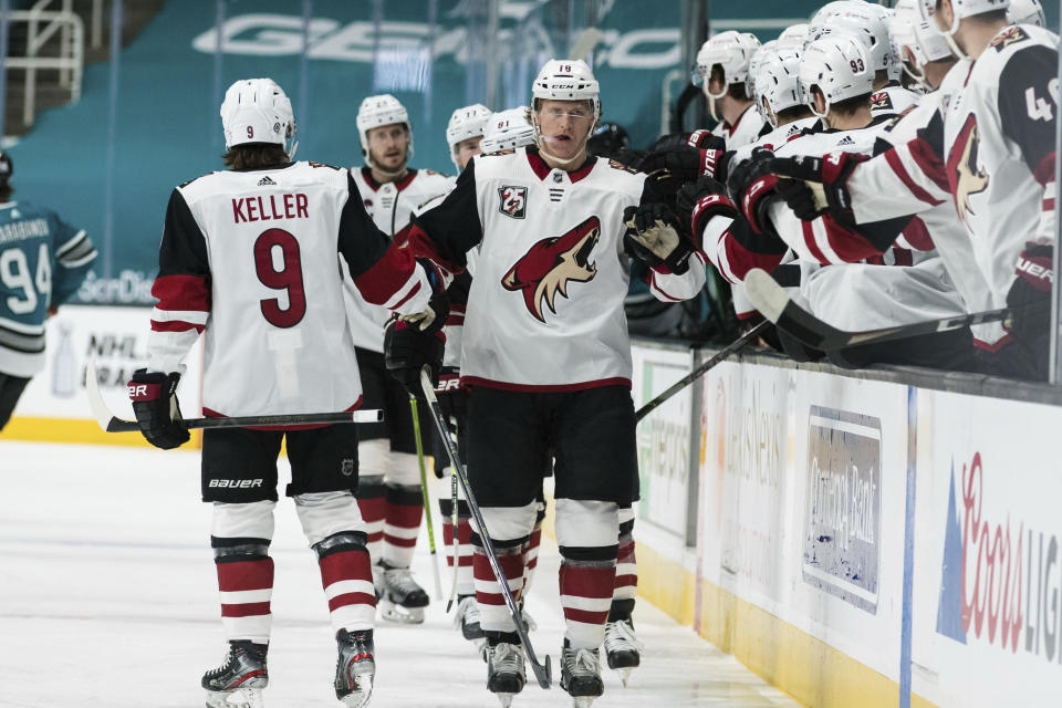 Arizona Coyotes center Christian Dvorak (18) is congratulated for his goal against the San Jose Sharks during the first period of an NHL hockey game in San Jose, Calif., Saturday, May 8, 2021. (AP Photo/John Hefti)