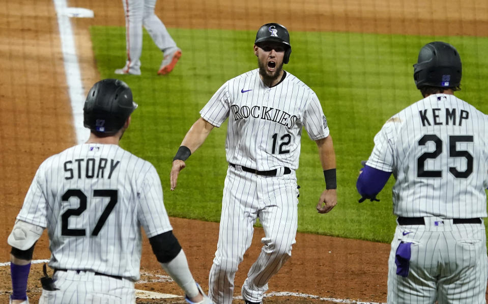Colorado Rockies' Chris Owings (12) celebrates a run with teammates Trevor Story (27) and Matt Kemp (25) against the San Francisco Giants during the sixth inning of a baseball game, Monday, Aug. 3, 2020, in Denver. (AP Photo/Jack Dempsey)