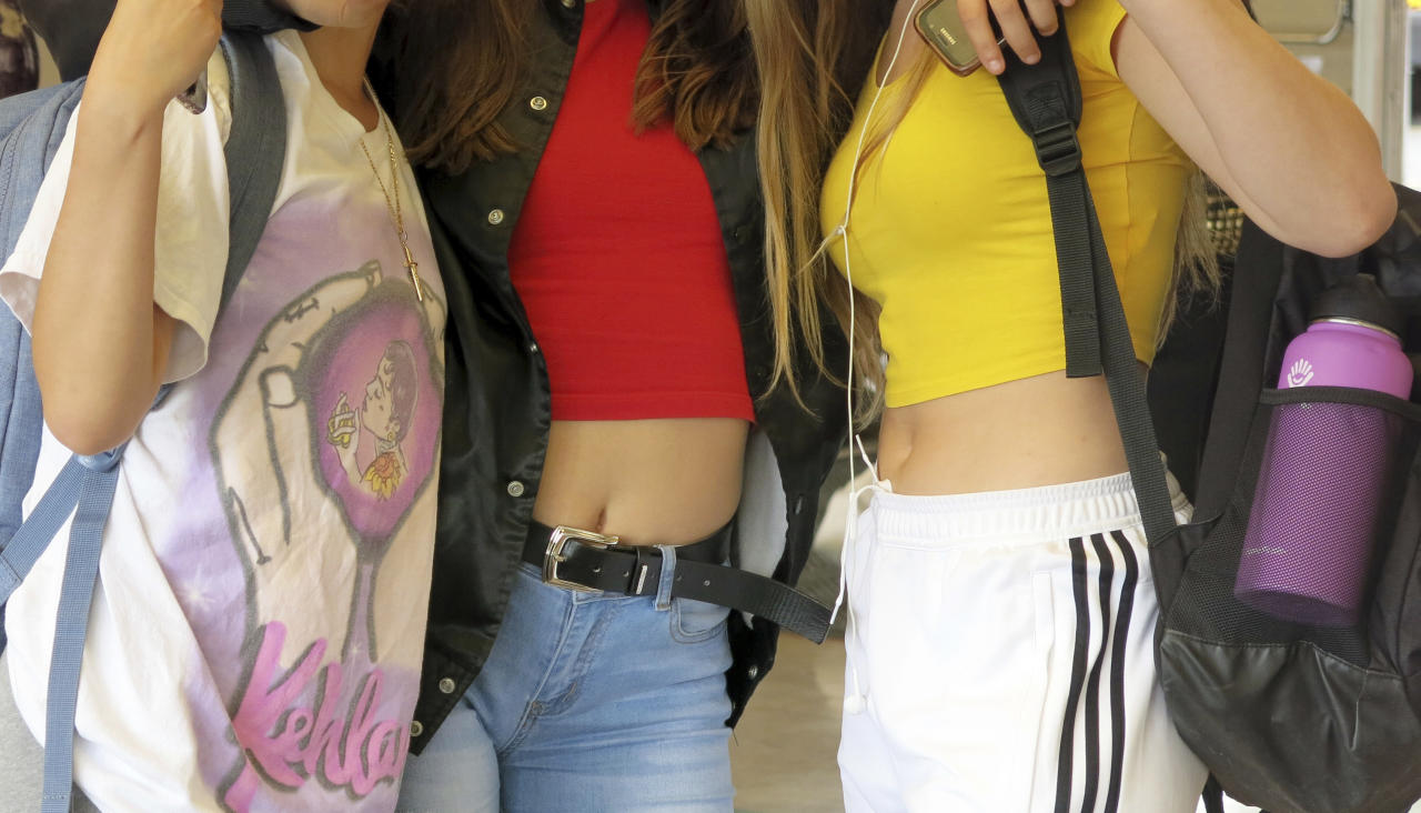 In this Sept. 7, 2018 photo, students socialize at Grant High School in Portland, Ore., after school let out. Portland Public Schools relaxed its dress code in 2016 after student complaints that the rules unfairly targeted female students and sexualized their fashion choices. (AP Photo/Gillian Flaccus)