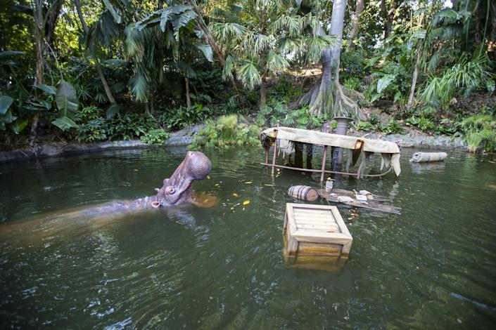 A view of floating wreckage from a boat among hippopotami during the Jungle Cruise ride