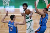 Boston Celtics guard Marcus Smart, center, passes the ball while trapped by Oklahoma City Thunder's Aleksej Pokusevski, left, and Darius Bazley, right, during the first half of an NBA basketball game, Tuesday, April 27, 2021, in Boston. (AP Photo/Charles Krupa)