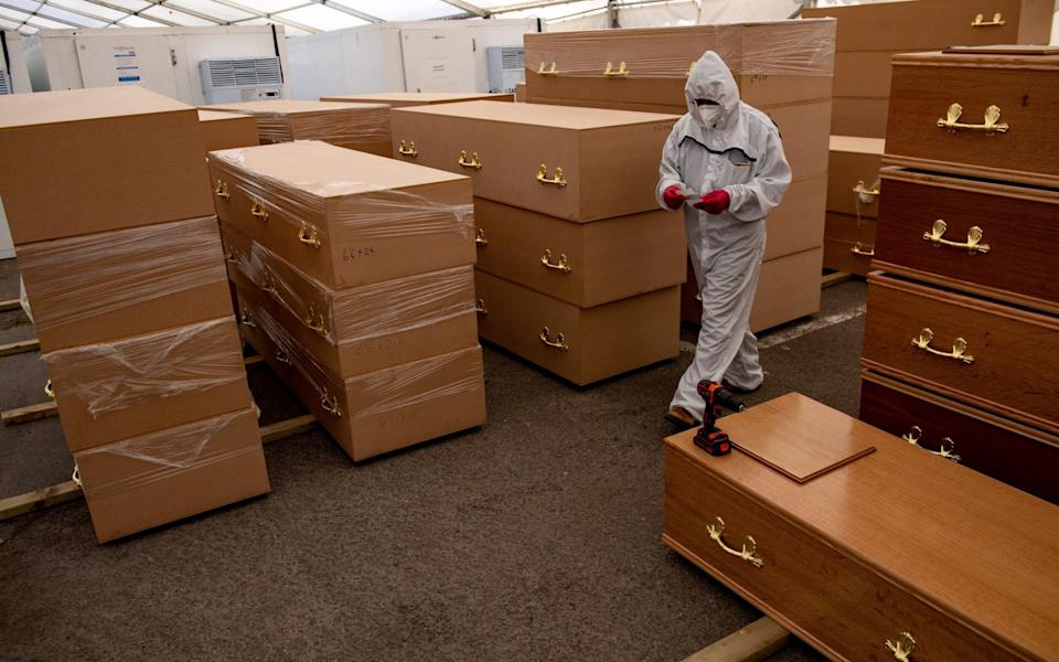 A volunteer walks by coffins at Central Jamia Mosque Ghamkol Sharif in Birmingham - Jacob King/PA
