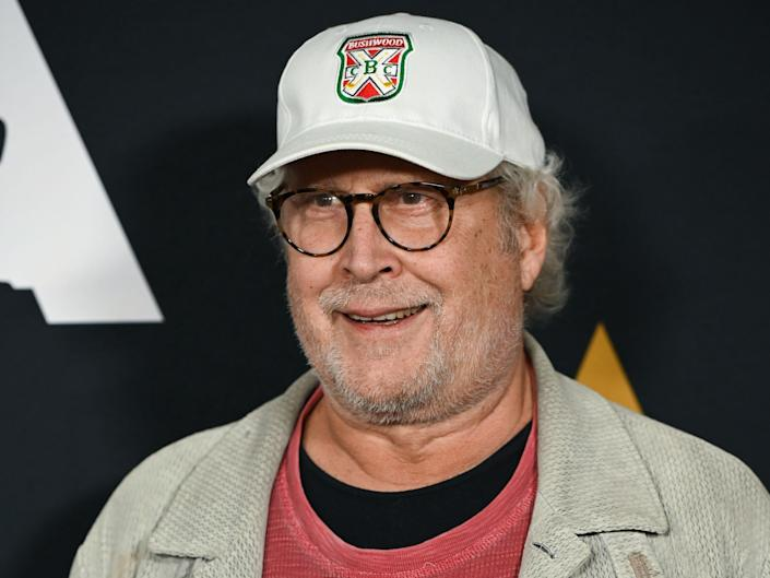 Chevy Chase at an event in 2019. He wears a red shirt under a gray jacket and a baseball hat.
