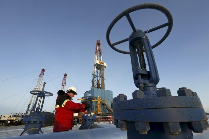 File photo of worker checking valve of oil pipe at Lukoil company owned Imilorskoye oil field outside West Siberian city of Kogalym