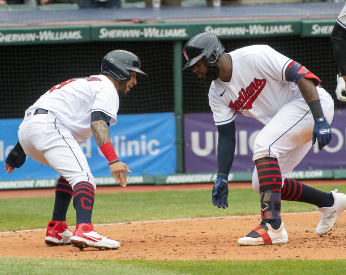 Cleveland Indians' Eddie Rosario, left, congratulates Franmil Reyes who hit a three-run home run off New York Yankees starting pitcher Jameson Taillon during the fourth inning of a baseball game in Cleveland, Sunday, April 25, 2021. (AP Photo/Phil Long)
