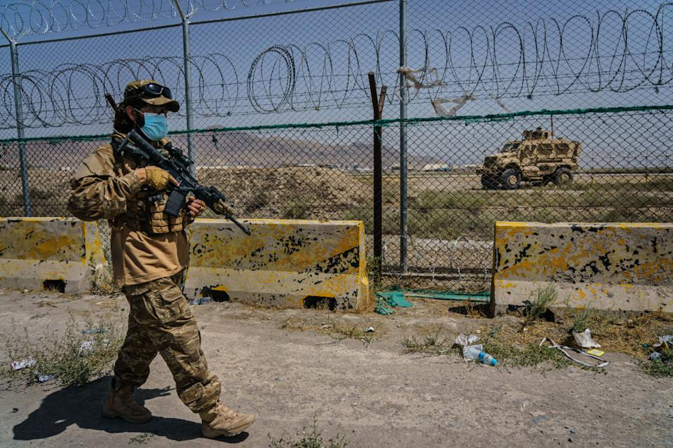 Taliban fighters secure the outer perimeter, in plain sight of the American forces that control the Hamid Karzai International Airport in Kabul. Source: Getty via LA Times