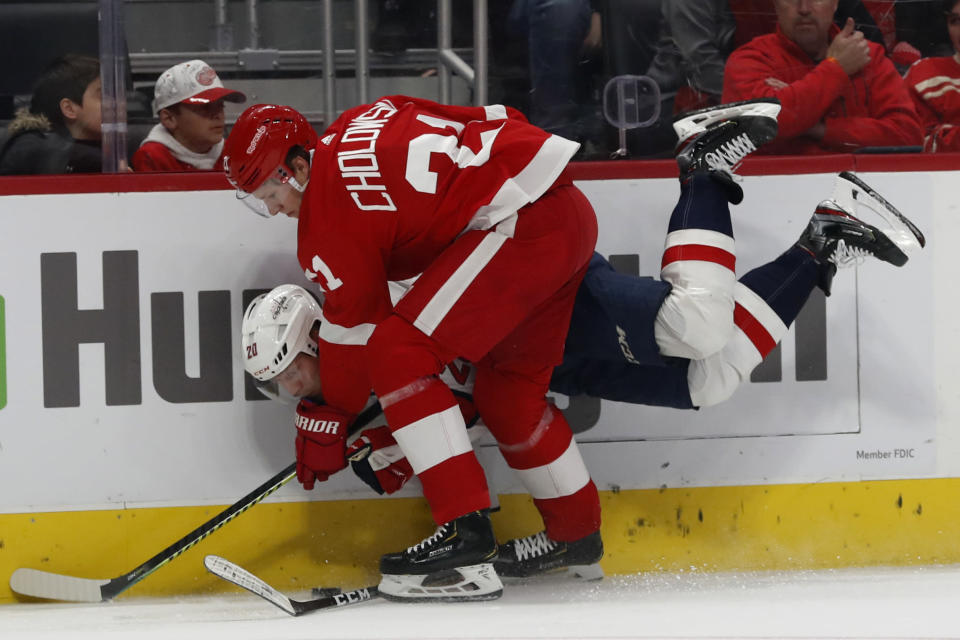 Detroit Red Wings defenseman Dennis Cholowski (21) checks Washington Capitals center Lars Eller (20) during the first period of an NHL hockey game Saturday, Nov. 30, 2019, in Detroit. (AP Photo/Carlos Osorio)