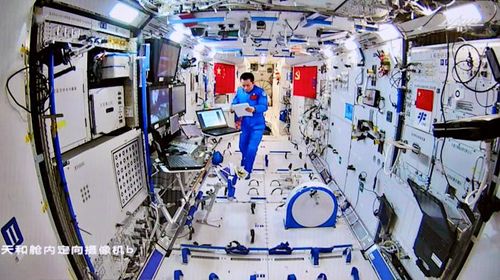 astronaut taikonaut in chinese space station looking at papers wearing blue jumpsuit