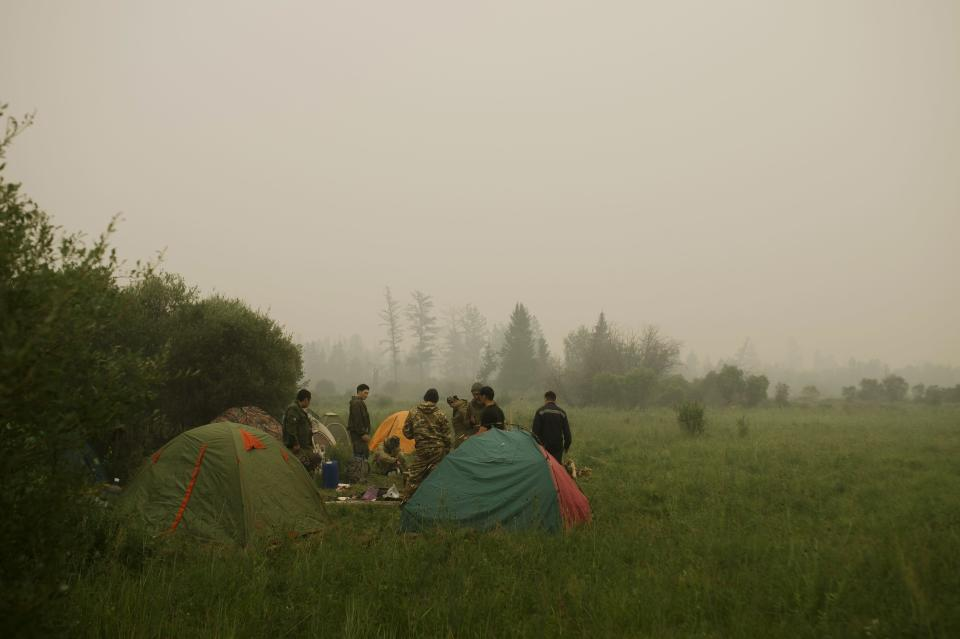 Member of volunteers crew rest at their tent camp at Gorny Ulus area west of Yakutsk, Russia, Tuesday, July 20, 2021. The hardest hit area is the Sakha Republic, also known as Yakutia, in the far northeast of Russia, about 5,000 kilometers (3,200 miles) from Moscow. Volunteers have joined over 5,000 regular firefighters in the effort, motivated by their love of the vast region. (AP Photo/Ivan Nikiforov)