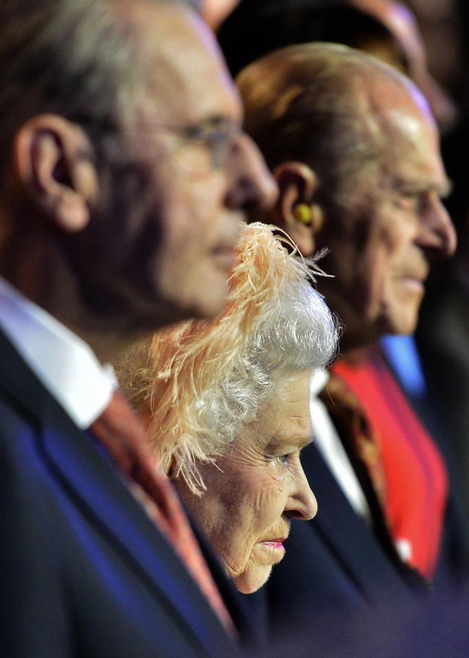 Britain's Queen Elizabeth II, center, Britain's Prince Philip, the Duke of Edinburgh, right, and IOC President Jacques Rogge, left, attend the Opening Ceremony of the 2012 Olympic Summer Games at the Olympic Stadium in London, Friday, July 27, 2012. (AP Photo/Toby Melville, Pool)