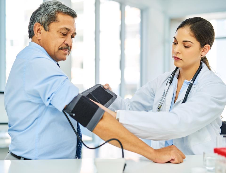 Scene doctor checking patient's blood pressure in hospital