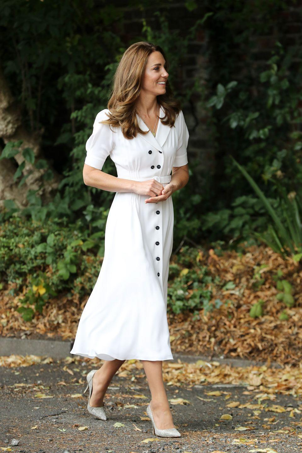 """<p>While visiting the charity, Baby Basic UK & Baby Basics Sheffield, Kate re-wore a crisp, white shirtdress by Suzannah, which she previously sported for <a href=""""https://www.townandcountrymag.com/society/tradition/a28258730/kate-middleton-white-dress-wimbledon-2019/"""" rel=""""nofollow noopener"""" target=""""_blank"""" data-ylk=""""slk:last year's Wimbledon match"""" class=""""link rapid-noclick-resp"""">last year's Wimbledon match</a>. When the Duchess entered the charity, she donned a <a href=""""https://www.townandcountrymag.com/society/tradition/g32616136/queen-elizabeth-princess-charlotte-royal-family-liberty-of-london-print-photos/"""" rel=""""nofollow noopener"""" target=""""_blank"""" data-ylk=""""slk:liberty print"""" class=""""link rapid-noclick-resp"""">liberty print</a> face mask. </p>"""