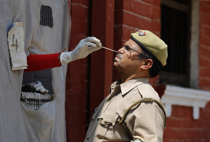 A health worker takes a nasal swab sample of a policeman to test for COVID-19 in Prayagraj, India, Saturday, May 8, 2021. Two southern states in India became the latest to declare lockdowns, as coronavirus cases surge at breakneck speed across the country and pressure mounts on Prime Minister Narendra Modi's government to implement a nationwide shutdown. (AP Photo/Rajesh Kumar Singh)