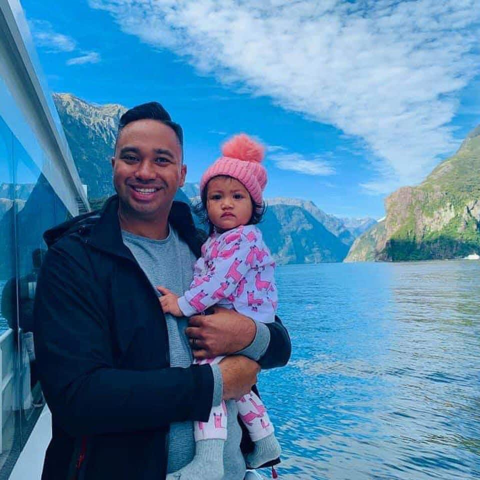 Harvee Pene holds his daughter Havana in front of a blue lake and mountains.