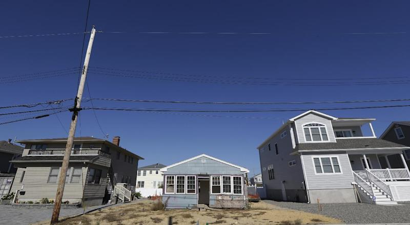 This Friday, Oct. 18, 2013 photo shows the vacation home of Cora Hoch, center, in Lavallette, N.J. The home, which was damaged by Superstorm Sandy, has been gutted and no repairs have been made to it while neighbor homes are up and running again. Billions of dollars in federal rebuilding and aid and insurance payments have helped many full-time Jersey shore residents to recover. But many property owners of modest means who had scrimped and saved to buy vacation homes on the shore, or may have inherited their getaway bungalows and cottages, have struggled to pull together enough money to hang on and rebuild. (AP Photo/Julio Cortez)