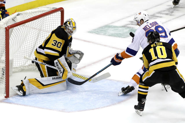 New York Islanders' Brock Nelson (29) puts a shot behind Pittsburgh Penguins goaltender Matt Murray (30) with Garrett Wilson (10) defending during the first period in Game 4 of an NHL first-round hockey playoff series in Pittsburgh, Tuesday, April 16, 2019. (AP Photo/Gene J. Puskar)