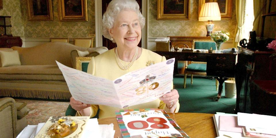 <p>The queen looked elated to read birthday cards in honor of her 80th birthday in the Regency Room at Buckingham Palace. </p>