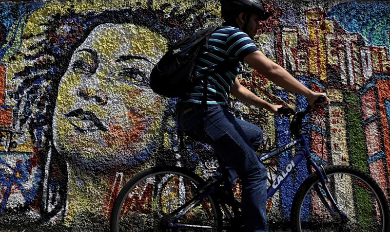 A man rides past a graffiti in tribute of late councilwoman Marielle Franco, murdered last year in Rio de Janeiro, Brazil April 18, 2019. REUTERS/Ricardo Moraes