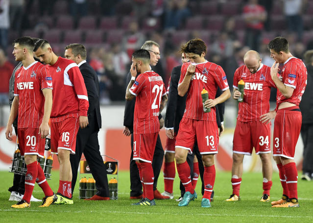 Cologne's head coach Peter Stoeger, center, and members of the team stay on the pitch after the Europa League group H soccer match