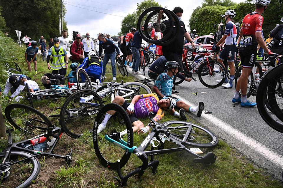 Italy's Kristian Sbaragli, left, and France's Bryan Coquard, right, lie on the ground after crashing during the first stage of the Tour de France cycling race over 197.8 kilometers (122.9 miles) with start in Brest and finish in Landerneau, France, Saturday, June 26, 2021. (Anne-Christine Poujoulat, Pool Photo via AP)