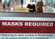 To prevent the spread of Covid-19, a sign directs travelers to wear masks at Love Field Tuesday, March 2, 2021, in Dallas. (AP Photo/LM Otero)