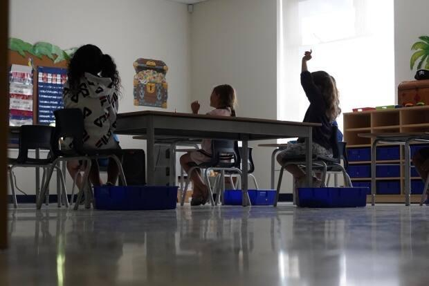 A student raises their hand during the first day of class at Ottawa's École élémentaire catholique Jonathan-Pitre in September 2020. (Francis Ferland/CBC - image credit)